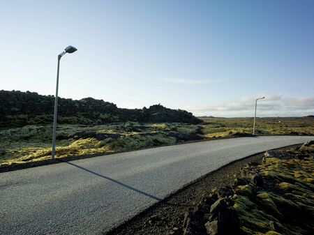 Country road in an area with green moss and small rocks in Iceland. Backplate for automobile industry and cgi. Stok Fotoğraf