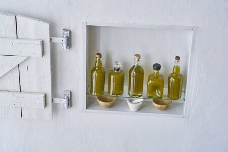 hous home design vintage wall shelf  Olive oil bottle five bottles food cooking mediterranean natural organic toscany country house healthy stylish white  kitchen  italy spain greece high angel shot Stok Fotoğraf