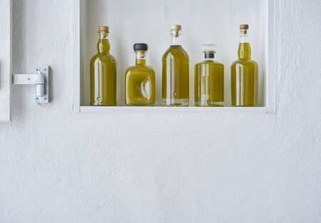 Olive oil oils glass bottle five bottles shelf food cooking mediterranean natural organic toscany beauty home country house healthy stylish white copy space copy space Stok Fotoğraf - 138033966