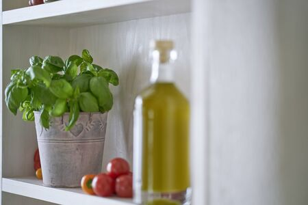 closeup kitchen shelf olive oil bottle pot parsley in mediterranean style, green yellow red vegetarian vegetable in sunny summer feeling,copy space blurred