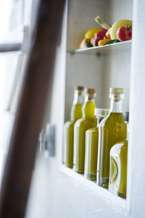detail closeup from a small shelf in country rural style house shop,bottles olive oil vegetable lemon tomatos,blurred wodden diffuse ladder in foreground