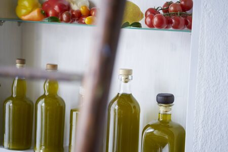 atmospheric detail closeup from a shelf in wall in country house rural style summer in spain.bottles oil vegetable paprika pepper lemon tomatos,blurred diffuse ladder in foreground