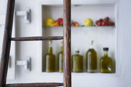 closeup from a wooden ladder rung with blurred diffuse background in a small shop house home kitchen in mediterranean style