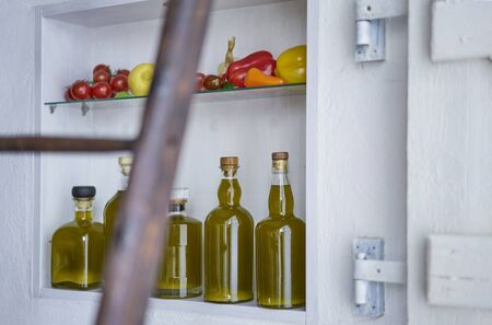detail closeup from a shelf in wall in country house rural style summer in spain.bottles oil vegetable paprika pepper lemon tomatos,blurred diffuse ladder in foreground