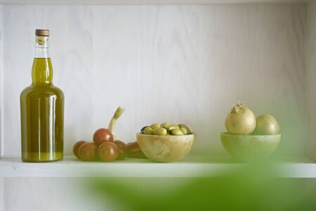 atmospheric closeup shelf bottle olive oil bowl with green olives and oniens tomatoes in kitchen hous home,blurry green leaf in foregrround,modern living food cooking natural organic Reklamní fotografie