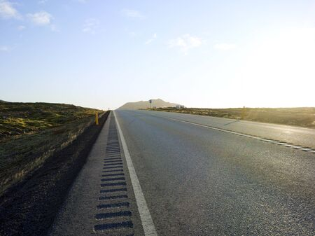 Country road in an area with open space  green moss and small rocks in Iceland Backplate for automobile industry with adventure asphalt background highland landscape road rural steppe untouched