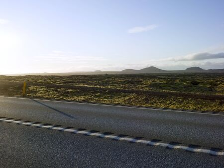 Highway,Country road in iceland  area Grindavík gunnuhver with open space  green yellow moss and small rocks. Backplate for automobile industry with adventure asphalt background highland landscape steppe untouched 스톡 콘텐츠