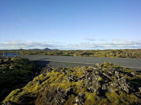 Highway or Country road in iceland with open space green yellow moss and small rocks Backplate for automobile industry with asphalt