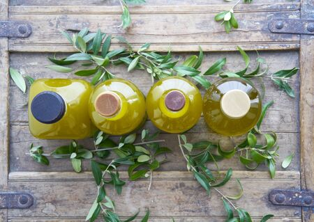 Closeup from above of four glass bottles oil golden liquid on a rustic shabby coffer surrounded by olive leaves mediterranean cooking house hotel restaurant Archivio Fotografico