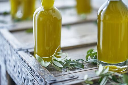 glass bottles filled with a golden liquid oil juice healthy fresh on a rustic wooden piece of furniture olive leaves around them. Gourmet luxury cooking book enjoyment pleasure