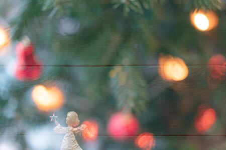 Christmas celebration card with a golden angel in front of a green background and surrounded by various colourful christmas lights Stok Fotoğraf