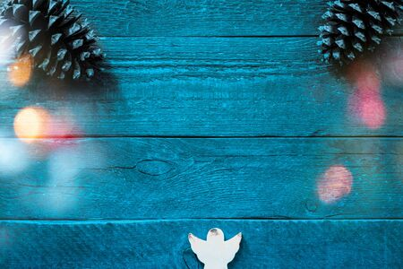 Christmas card with fir cones and an angel in front of a blue background with colourful christmas lights