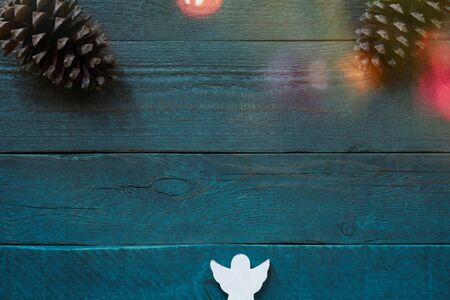 Christmas card with fir cones and an angel in front of a rustic blue-green background and with colourful christmas lights