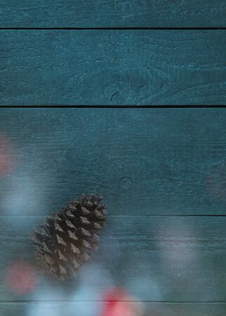 Christmas card with a fir cone and colourful christmas lights in front of a rustic blue-green background