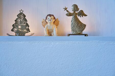 Christmas decoration with angels and candles in a pure white shelf in a white wall, gold silver bright mood and copy space Stok Fotoğraf