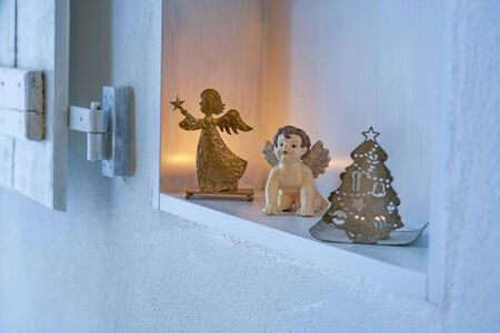 Christmas decoration with angels and candles in a pure white shelf in a white wall, gold silver bright mood for celebration card