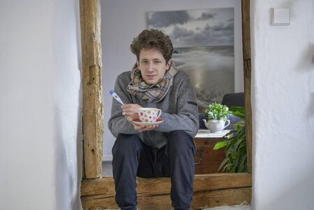 Young man feeling under the weather, sitting with a cup of tea and a thermometer and a scarf in a door frame