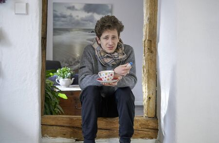 Young suffering man feeling under the weather, sitting with a cup of tea and a thermometer and a scarf in a door frame