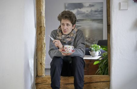 Young curly man feeling under the weather, sitting with a cup of tea and a thermometer and a scarf in a door frame Stok Fotoğraf