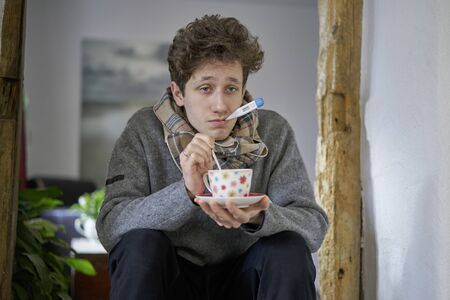 A sick young man with a cold sitting in his house has a thermometer in his mouth and is holding a cup in his hand