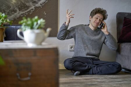 Young amused man calling with a mobile phone while sitting on the floor of his apartment