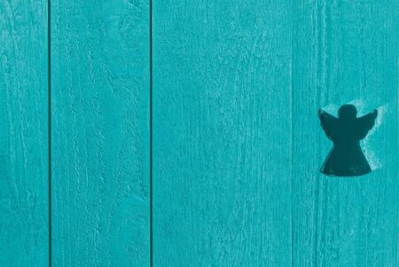 Blue-green textured wooden planks with an angel, background and copy space
