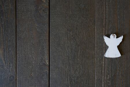 Dark background of wood with structure and a white angel, card and copy space