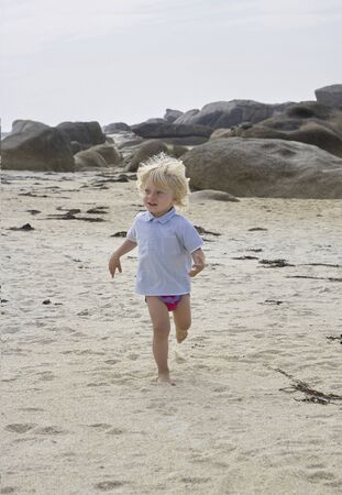 Happily smiling cute little boy running in the sand at a beach, summer holiday feeling , rocks in the background Stok Fotoğraf