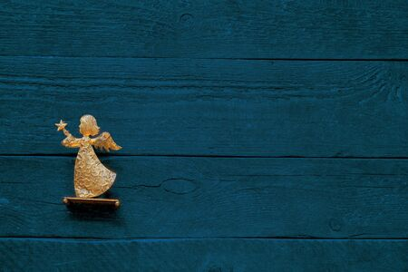 Colourful blue-green background of textured wooden planks with a bright golden angel, card and copy space Stok Fotoğraf