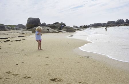 Cute little boy standing in the sand of a beautiful beach in Brittany,  imitating taking a picture of the sea