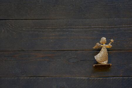 Background of textured wooden weathered planks with a bright golden angel, card and copy space