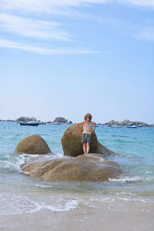 Handsome boy standing on round rocks in the sea at a beach, hands on a rock, posing for a picture, small nice boats in the background Stok Fotoğraf