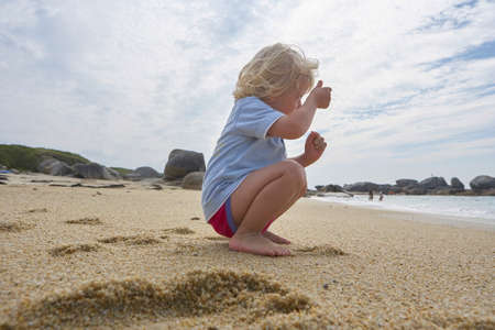 Cute little boy sitting in the sand of a beach, imitating taking a picture of the sea