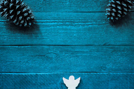 Colourful blue wooden planks with structure and copy space, two fir cones and an angel