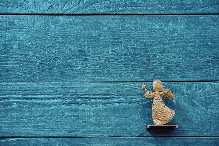 Colourful background of textured wooden planks in blue-green with a golden angel and copy space
