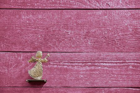 Colourful textured red wooden planks with a golden angel and copy space, backdrop