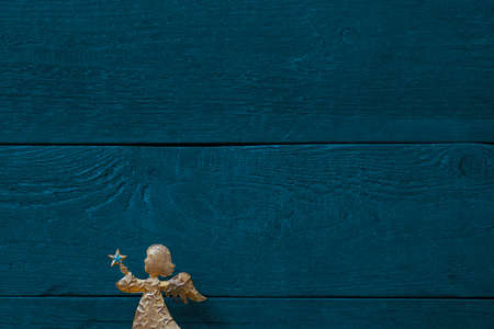 Golden angel in front of colourful blue-green background of textured wooden planks, copy space