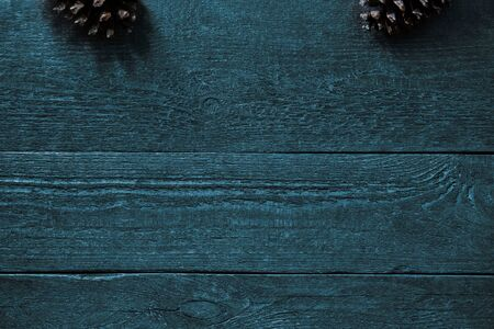 Beautiful bluegreen wooden background with structure and fir cones, postcard
