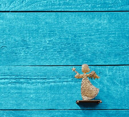 Colourful background of textured wooden planks in blue with a golden angel and copy space