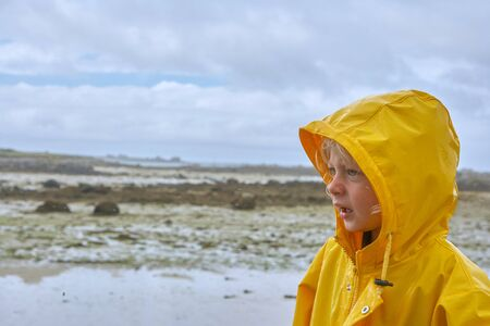 Cute little child in a yellow raincoat, not looking very satisfied, beach at low tide in the unsharp background