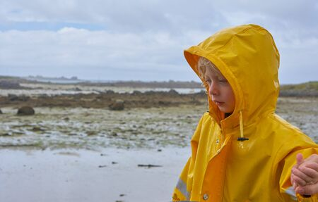 Cute little child in a yellow raincoat trustfully holding the mother's hand, beach at low tide in the unsharp background Stok Fotoğraf