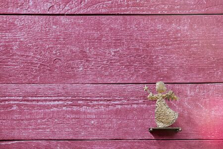Colourful textured red wooden planks with a golden angel and copy space, background Stok Fotoğraf