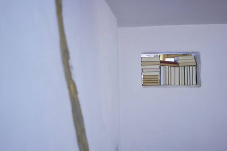Set of books placed inside rectangle space in white wall dark open plan room bright interior Stock Photo
