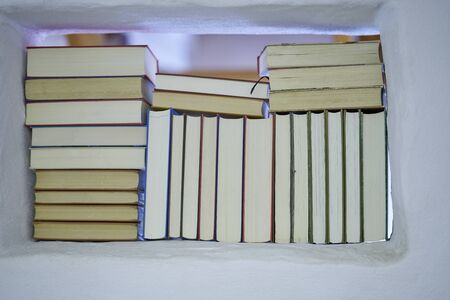 Detail of back of assortment of books in a white shelf with view to the next room in a white textured wall, closeup bright and friendly Stok Fotoğraf