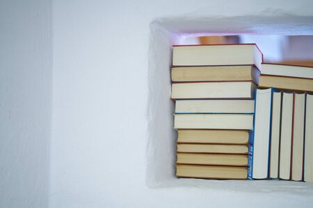 Detail of an assortment of books in a white shelf in a white textured wall in a room with copy space, back of books