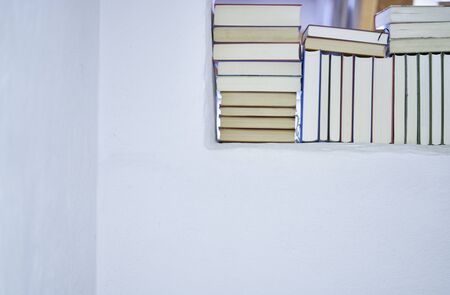 Bright detail of an assortment of books in a white textured wall in a room in a mediterranean country house with copy space