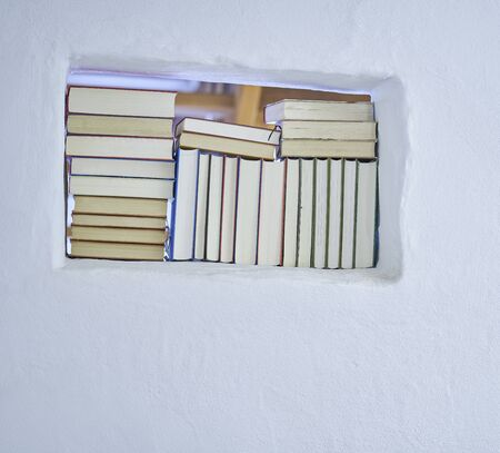 Bright sunny detail of an assortment of books in a white shelf in a white textured wall with copy space, back of books