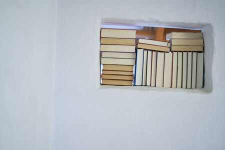 Bright sunny detail of an assortment of books in a room with white textured wall in a mediterranean country house, space in the wall with view to the next room Stok Fotoğraf