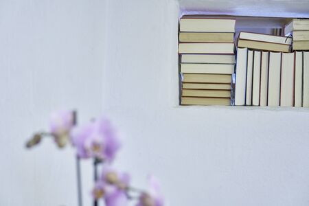 Detail of an organized stack of books in a white textured wall of a country house with copy space, unsharp orchid in the foreground