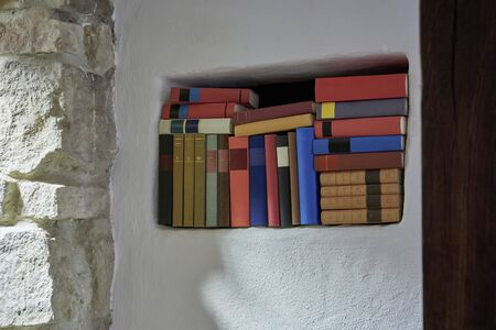 Book shelf inside white textured wall in white open plan room bright interior wide angle stone wall